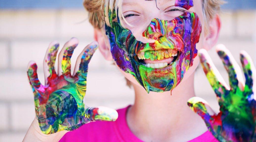 garçon souriant avec peinture sur les mains et le visage